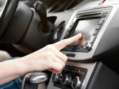 Finger on dashboard with gps panel and tv, dvd, audio system — Stockfoto