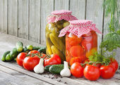 Canned tomatoes and pickled cucumbers, homemade preserved vegeta — Stock Photo