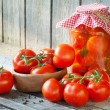 Homemade tomatoes in glass jar. Fresh and canned tomatoes on woo — Foto Stock