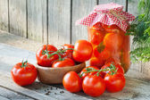 Homemade tomatoes in glass jar. Fresh and canned tomatoes on woo — Zdjęcie stockowe