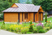 Village wooden house with flower bed — Stock Photo