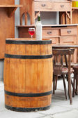 Wooden barrel with bottles of wine and glass, chair and table in — Стоковое фото