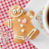 Gingerbread man and coffee cup on table — Stock Photo