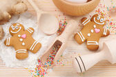 Funny gingerbread men, flour, rolling pin, spoon and ginger on k — Stock Photo