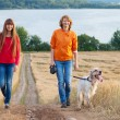 Mother and her daughter with dog walking outdoors — Stock Photo