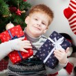 Happy smiling little boy with christmas gift boxes near the Chri — Stock Photo
