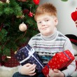 Happy smiling little boy with christmas gift boxes near the Chri — Stock Photo #36574713
