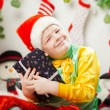 Happy smiling little boy with christmas gift boxes near the Chri — Stock Photo #36574869