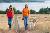 Mother and her daughter with dog walking outdoors — Stockfoto