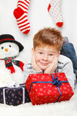 Happy smiling little boy with Christmas gift boxes — Stock Photo