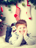 Happy smiling little boy near the Christmas tree — Stock Photo