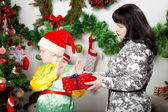 Boy refusing Christmas gift box from mother — Stock Photo