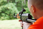 Man aiming at a target and shooting an automatic rifle for strik — Stock Photo