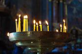 Vários altas velas acesas em um quarto escuro na igreja — Fotografia Stock