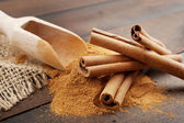 Cinnamon sticks and cinnamon powder in wooden scoop, on table — Stock Photo