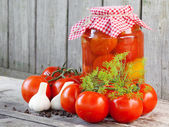 Homemade tomatoes in glass jar. Fresh and canned tomatoes on woo — Photo