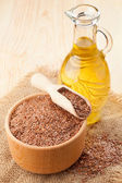 Mortar of flax seeds with wooden scoop and linseed oil in glass — Stock Photo