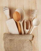 Wooden kitchen utensils:spoons, rolling pin, scoop and honey dip — Stock Photo