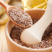 Mortar with flax seeds, linseed in wooden spoon — Stockfoto