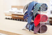 Set of rolled up neck ties on plastic shelf — Stock Photo