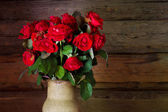 Beautiful roses with frech and wilted buds in ceramic jug on rus — Stock Photo
