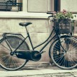 Vintage stylized photo of Old bicycle carrying flowers — Stock Photo #40455597