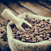 Vintage stylized photo of sack with coffee beans — Stock Photo