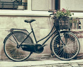 Vintage stylized photo of Old bicycle carrying flowers — Stock Photo