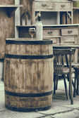 Vintage stylized photo of wooden barrel with bottles of wine and — Stock Photo