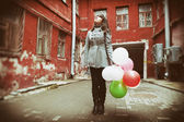 Teenager girl with colorful balloons on street — Stock Photo