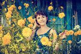 Beautiful woman near yellow flowers — Stock Photo
