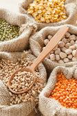 Sacos de hessian com trigo, grão de bico, lentilhas vermelhas e caneca verde — Fotografia Stock