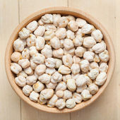 Chickpeas in wooden bowl, on wooden kitchen table — Stock Photo