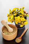 mortar on table and bucket with coltsfoot flowers, herbal medic — Stockfoto