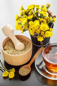 Healthy tea, bucket with coltsfoot flowers and wooden mortar on  — Stock Photo