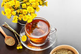 Healthy tea closeup, bucket with coltsfoot flower — Stock Photo