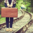 Young woman with old suitcase on railway — Stock Photo #46770651