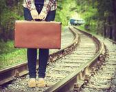 在铁路上的旧手提箱的年轻女子 — 图库照片
