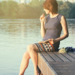 Relaxing young woman with a notebook in hand in city park near — Stock Photo