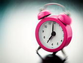 Pink Alarm clock ringing on bedside table — Stock Photo
