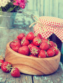 Strawberries in wooden bowl and jam — Stockfoto