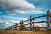 Wooden rustic fence in village and blue sky — Stock Photo