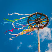 Celebration of Midsummer. Wooden wheel with bright ribbons — Stock Photo