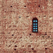 Small arched window in a red brick — Stock Photo