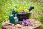 Black mortar with healing herbs and sage, glass bottle of oil — Stock Photo