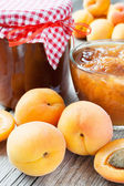 Ripe apricot fruits and jar of jam on table — Stock Photo
