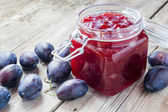 Plums and jar of jam on table — Stockfoto