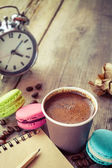 Macaroons, espresso coffee cup, sketch book and alarm clock on w — Stock Photo