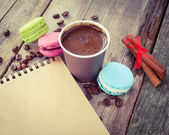 Macaroons, espresso coffee cup, cinnamon sticks and sketch book  — Stock Photo
