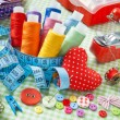 Spools of colorful thread, buttons, fabrics, measuring tape, pin — Stock Photo #51472867